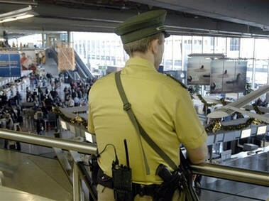 A German police officer watches passengers