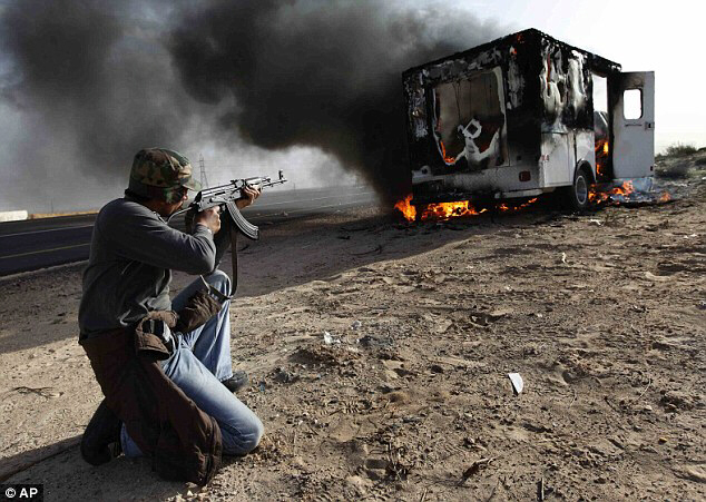 A Libyan rebel shoots at a pro-Gaddafi vehicle after oil fields were seized in Brega overnight