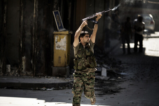 A Syrian rebel fires at a position held by regime forces