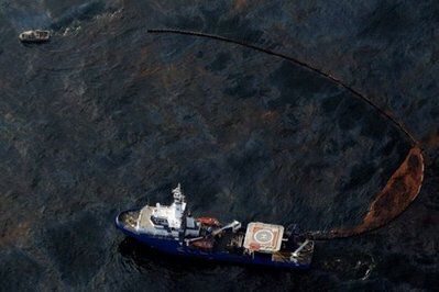 A boat uses a protective boom to collect oil leaking from the Deepwater Horizon wellhead in the Gulf of Mexico. A giant oil slick threatened Thursday to pollute the fragile wetlands of Louisiana, as officials warned that toxic crude was pouring into the Gulf of Mexico five times faster than previously thought.  (AFP/Getty Images/Chris Graythen)