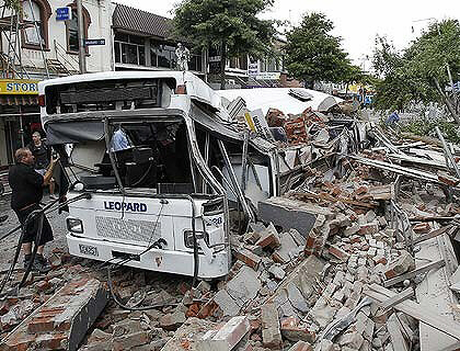 A bus crushed by falling building debris in Christchurch