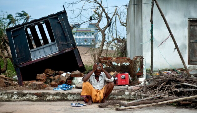 A coconut seller sits in front of his destroyed shop
