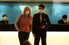 A hotel guest and a staff member in quarantine wear protective masks.