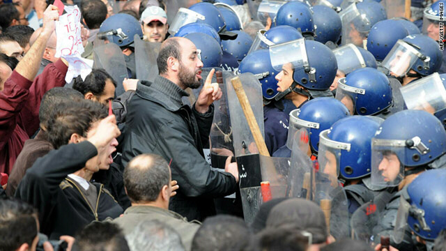 A man gestures towards Algerian police surrounding demonstrators