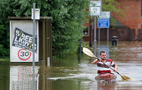 A man is forced to use a canoe for transport in Tewkesbury.