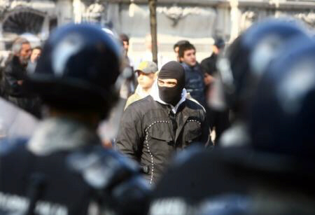A masked rioter faces a police cordon in Belgrade