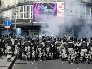 A phalanx of riot police clash with missile throwing protesters