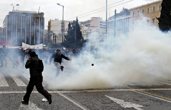 A protester kicks a tear gas canister at riot police during clashes in Athens