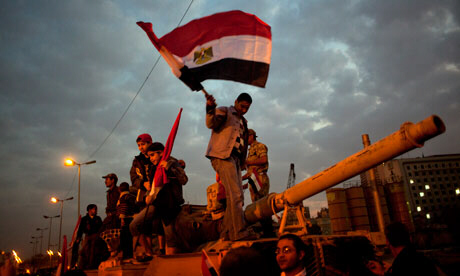 A protester waves an Egyptian flag on top of a tank