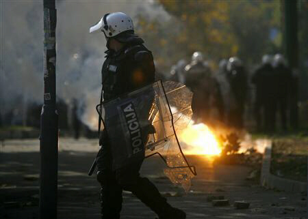 A riot policeman holds a smashed shield during clashes