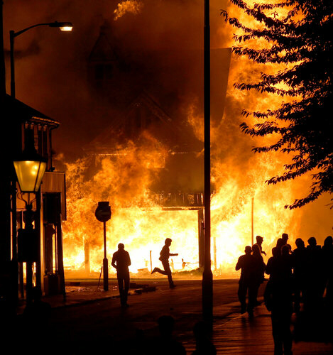 A shop was set on fire Monday in Croydon, south London. The home secretary said there had been hundreds of arrests. Sang Tan/Associated Press