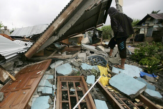 A villager checks damage in Central Aceh, Indonesia