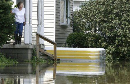 A woman stands stranded on her front porch Wednesday, Aug. 22, 2007, following heavy rains