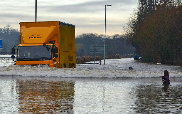 A woman stands waist-deep in floodwater as lorry tries to drive through