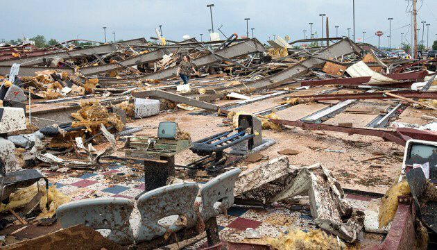 A woman walks through debris in Moore on May 20, 2013