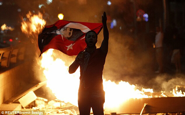 An anti-government protester holds Turkey's national flag