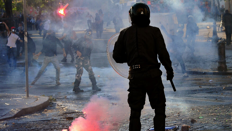 An anti-riot police officer reacts as protesters throw flares. The Piazza San Giovanni transformed into a battleground between police and protesters.