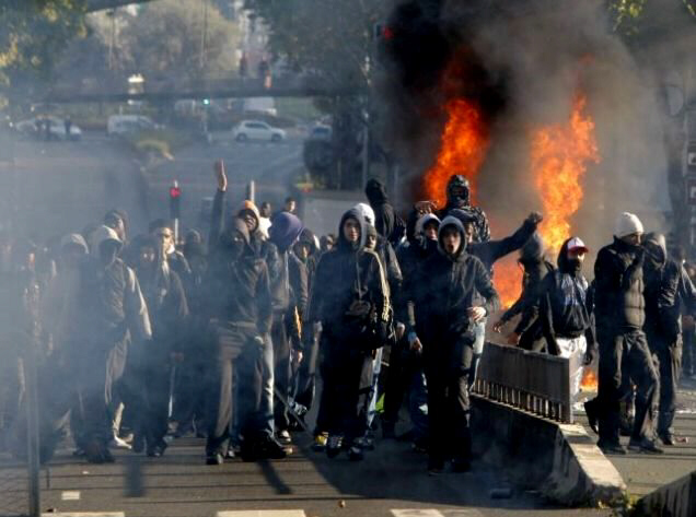 Fighting talk: Angry youths torch cars outside Paris Picture: AP