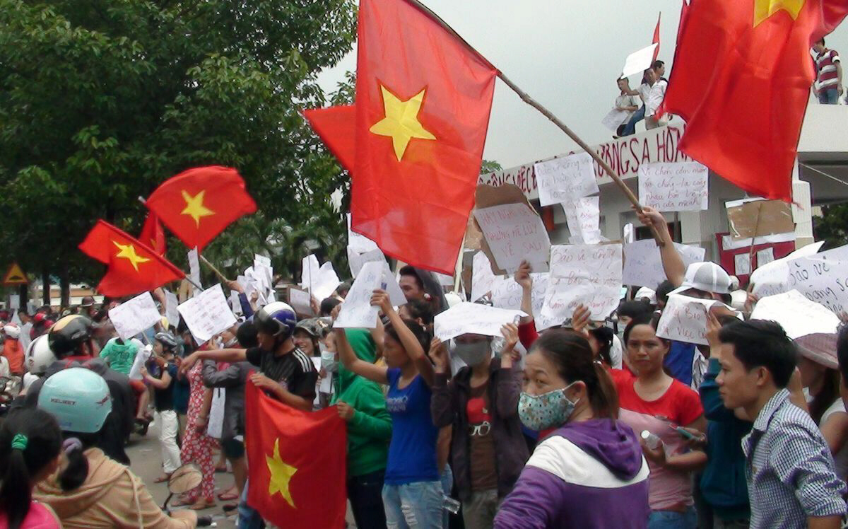 Anti-China Protesters wave flags and hold placards on a street outside a factory building in Binh Duong, Vietnam. China's placement of the rig off the coast of Vietnam set off violent anti-China protests in Vietnam this month. Photographer: VNExpress/AFP/Getty Images.