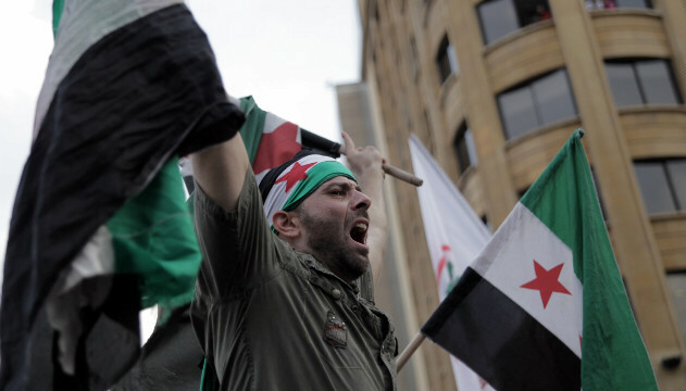 Anti-government protester waves a pre-Baath Syrian flag