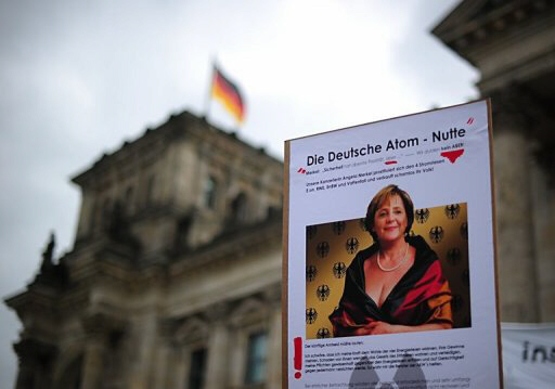 Anti-nuclear protestors hold up placard of Angela Merkel