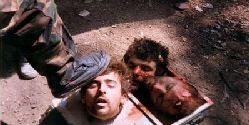 Decapitated heads under a camp guard's foot