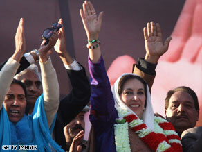 Bhutto (center) waves to supporters at a campaign rally minutes before she was assassinated