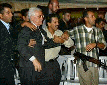 Bodyguards direct Mahmoud Abbas after gunfire erupted in a tent where people were mourning Yasser Arafat
