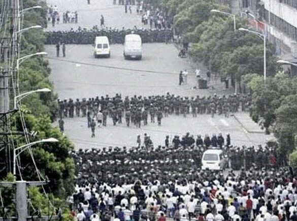 Chinese police officers block protesters after riot