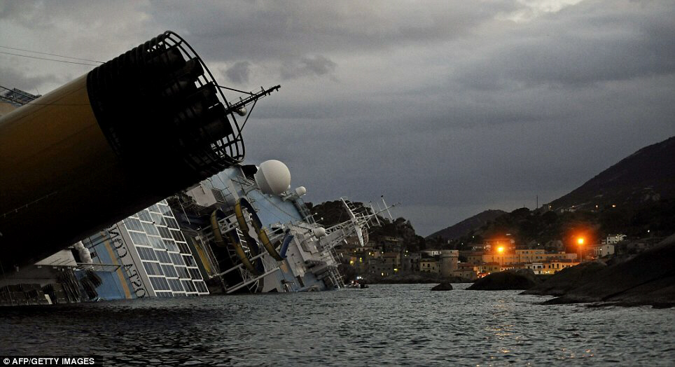 Costa Concordia pictured last night dangerously keeled over off the Giglio Island