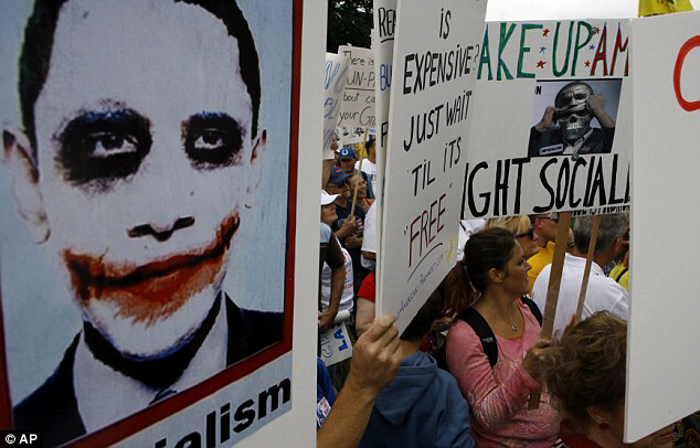 Demonstrators hold up Obama joker banners