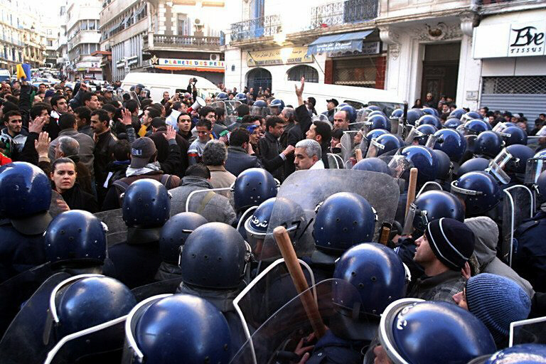 Demonstrators face riot police in Algiers, capital city of Algeria