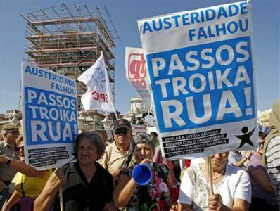 Demonstrators hold placards during a protest against austerity in Lisbon