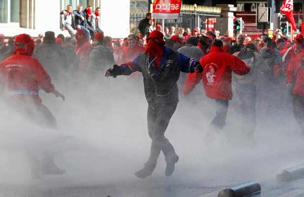 Demonstrators in Brussels are sprayed by water canons