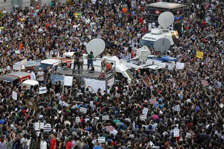 Demonstrators listen to a speaker on top of a platform in Madrid's Puerta del Sol May 20, 2011. REUTERS/Paul Hanna
