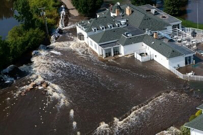 Flood waters begin to pour through a breached levee in North Dakota