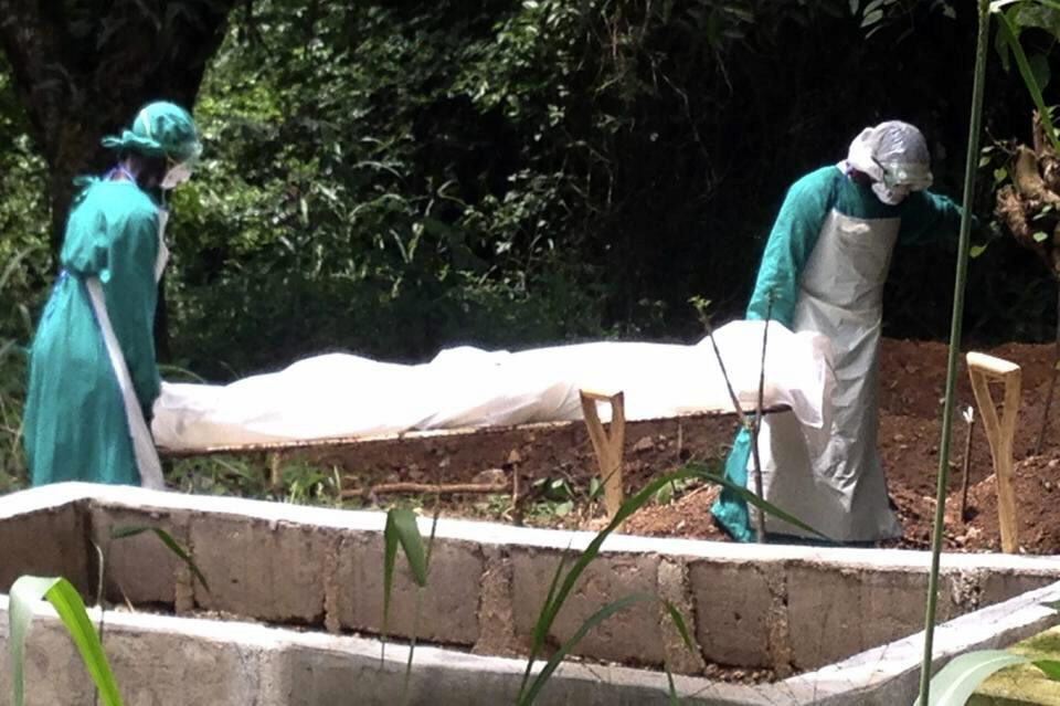 Health workers carry the body of an Ebola virus victim