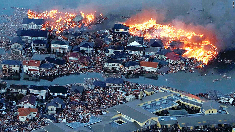Houses swept out to sea burn in the aftermath of the quake