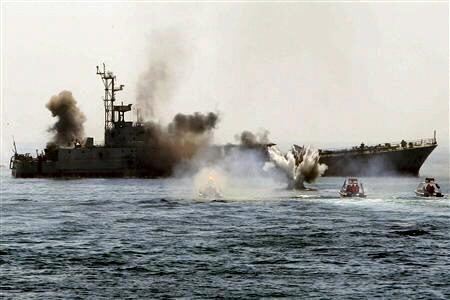 Iranian warship and speed boats in Strait of Hormuz