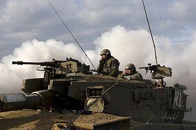 Israeli soldiers look out from atop a tank