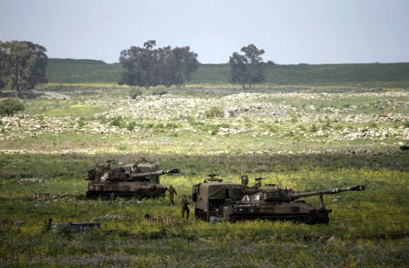 Israeli soldiers walks beside mobile artillery units near Golan Heights