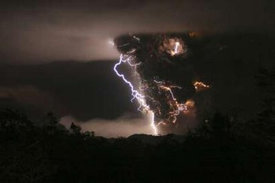 Lightning bolts appear above and around the Chaiten volcano