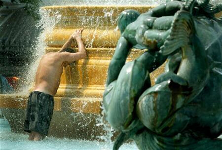 Man lowers his head as he cools off in fountain at Trafalgar Square