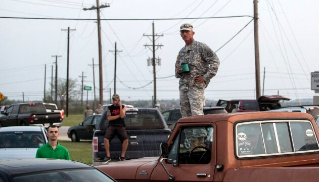 Military personnel and civilians wait outside Fort Hood for updates