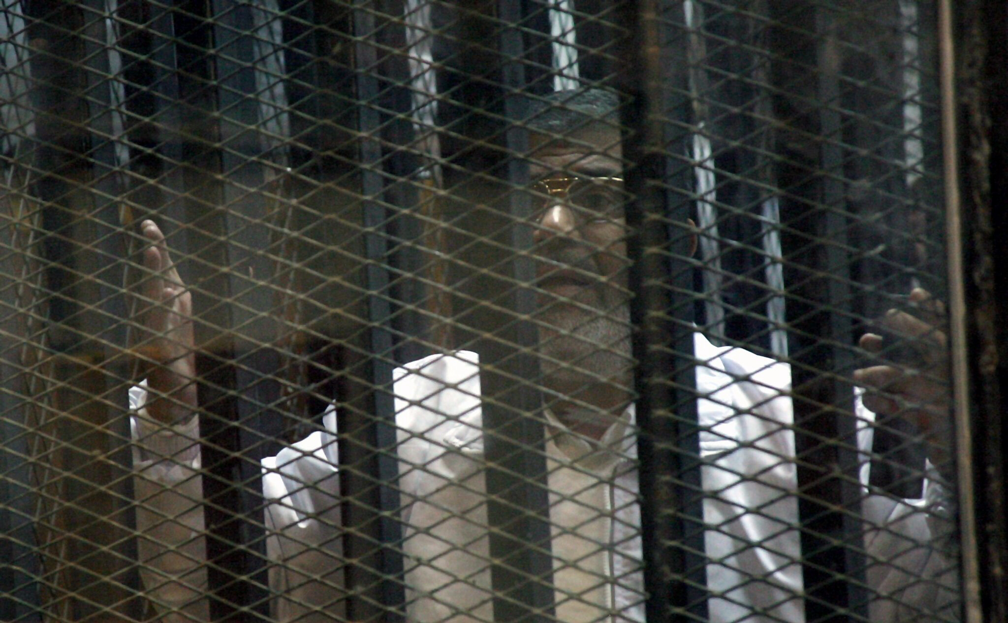 Ousted Egyptian president Mohamed Morsi looks helplessly from soundproof cage. Morsi faces execution by hanging if given the death sentence for any one of several crimes he is being charged with.