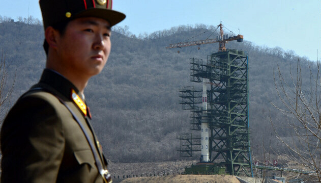 North Korean soldier stands guard in front of an Unha-3 rocket