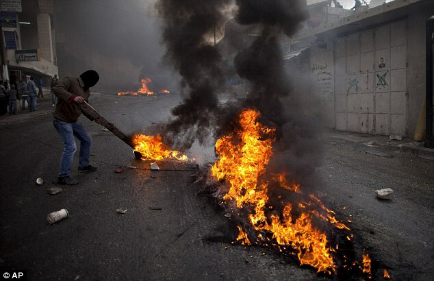 Palestinian protester stokes a burning barricade