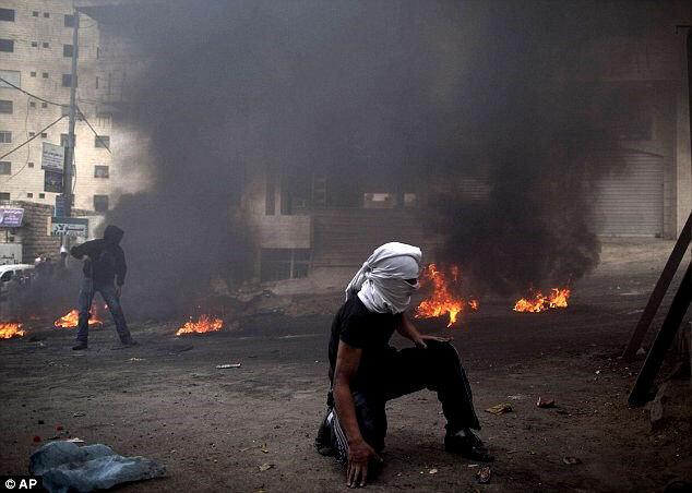 Palestinian protesters take position during clashes with Israeli soldiers