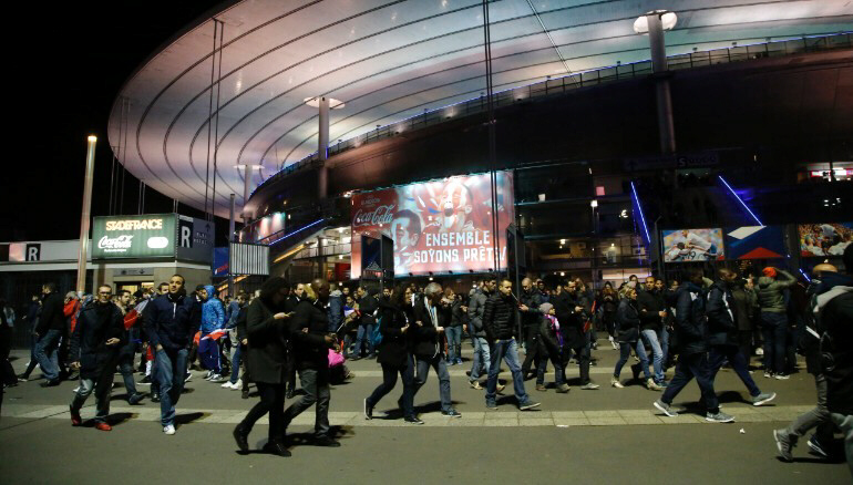 People leave the Stade de France after explosions were heard