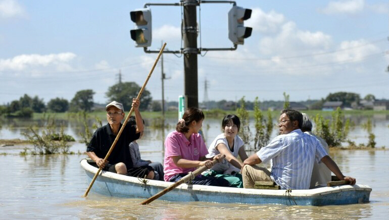 People paddle boat on flooded road in Joso, Japan